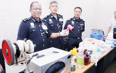 MOHD. SHUKRI (kiri) menunjukkan sebahagian dadah dan peralatan memproses dadah yang dirampas di Malim Nawar di Ipoh semalam.