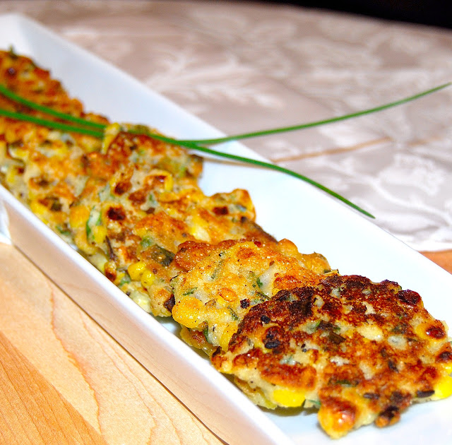 White rectangular dish with golden corn fritters topped with chives.