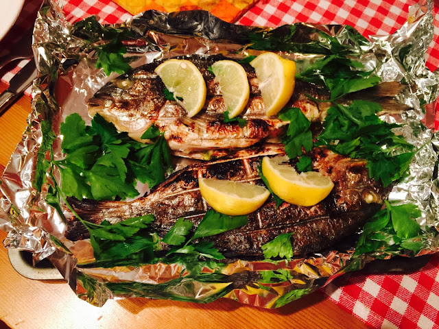 Serving platter of barbecued feta stuffed Greek sea bream