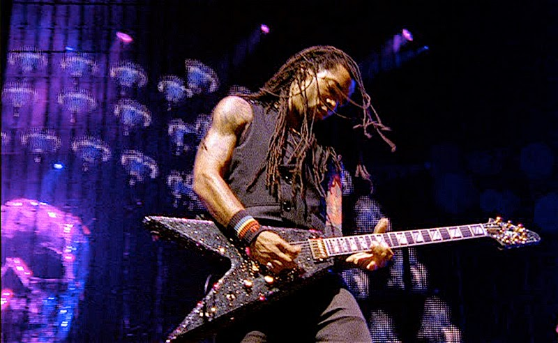 A man with dreadlocks plays a guitar.