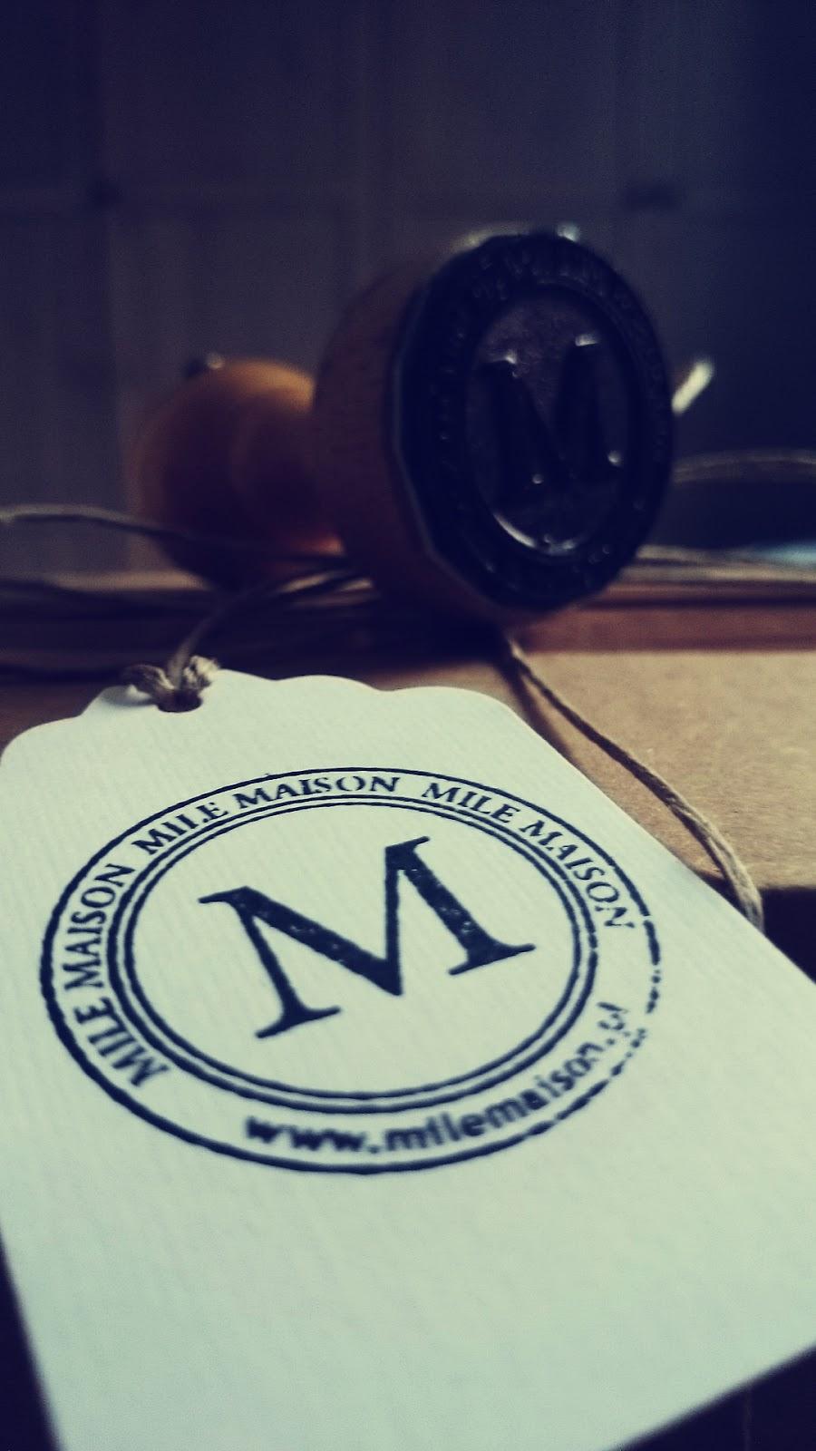 Drewniana pieczęć wnętrzarskiego sklepu Mile Maison i etykietka z pieczęcią