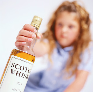 Young girl holding a whiskey bottle.