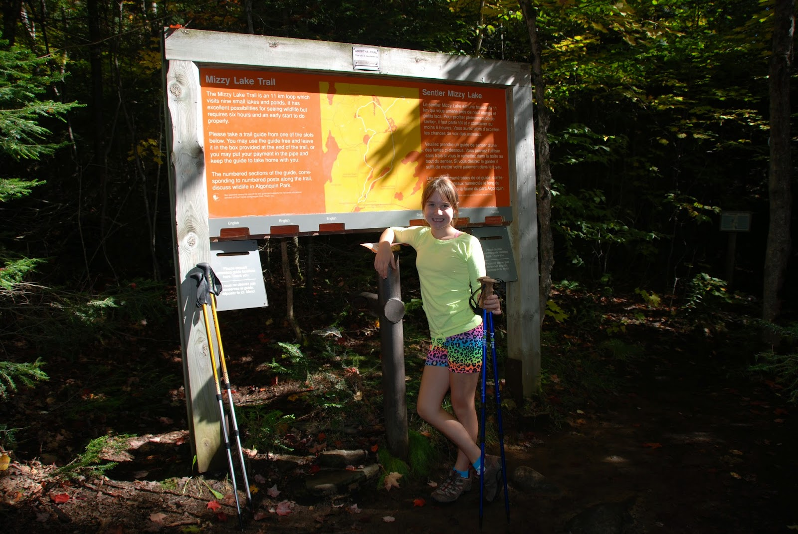 A hiker stands at the trail sign of the Mizzy Lake trail