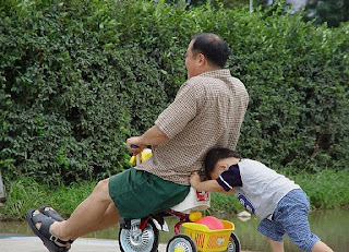 funny picture child pushes father on his tricycle