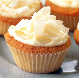 Creamy coconut cupcakes. White cupcakes with a cream cheese frosting and coconut shaving garnish.