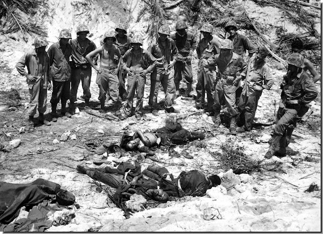U.S. Marines inspect bodies three Japanese soldiers killed  invasion Peleliu island Palau group  September 16, 1944.