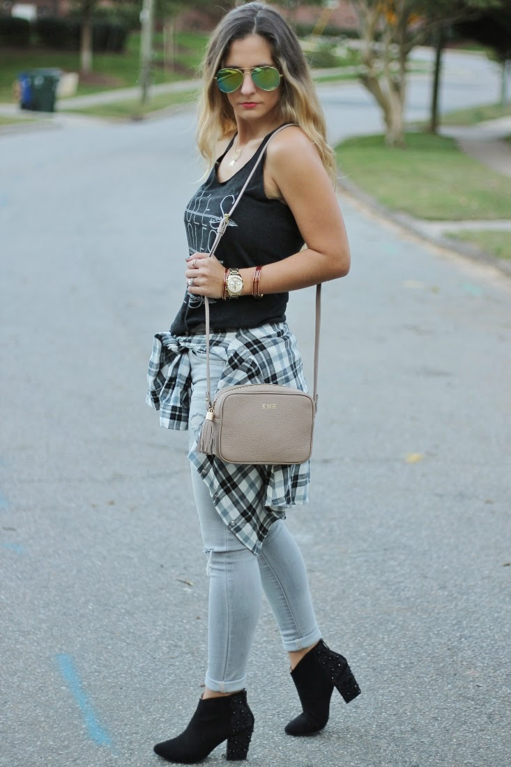 Gray skinny jeans with tank top and flannel shirt tied around waist
