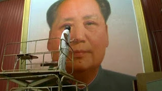 Man touches up gigantic Mao portrait
