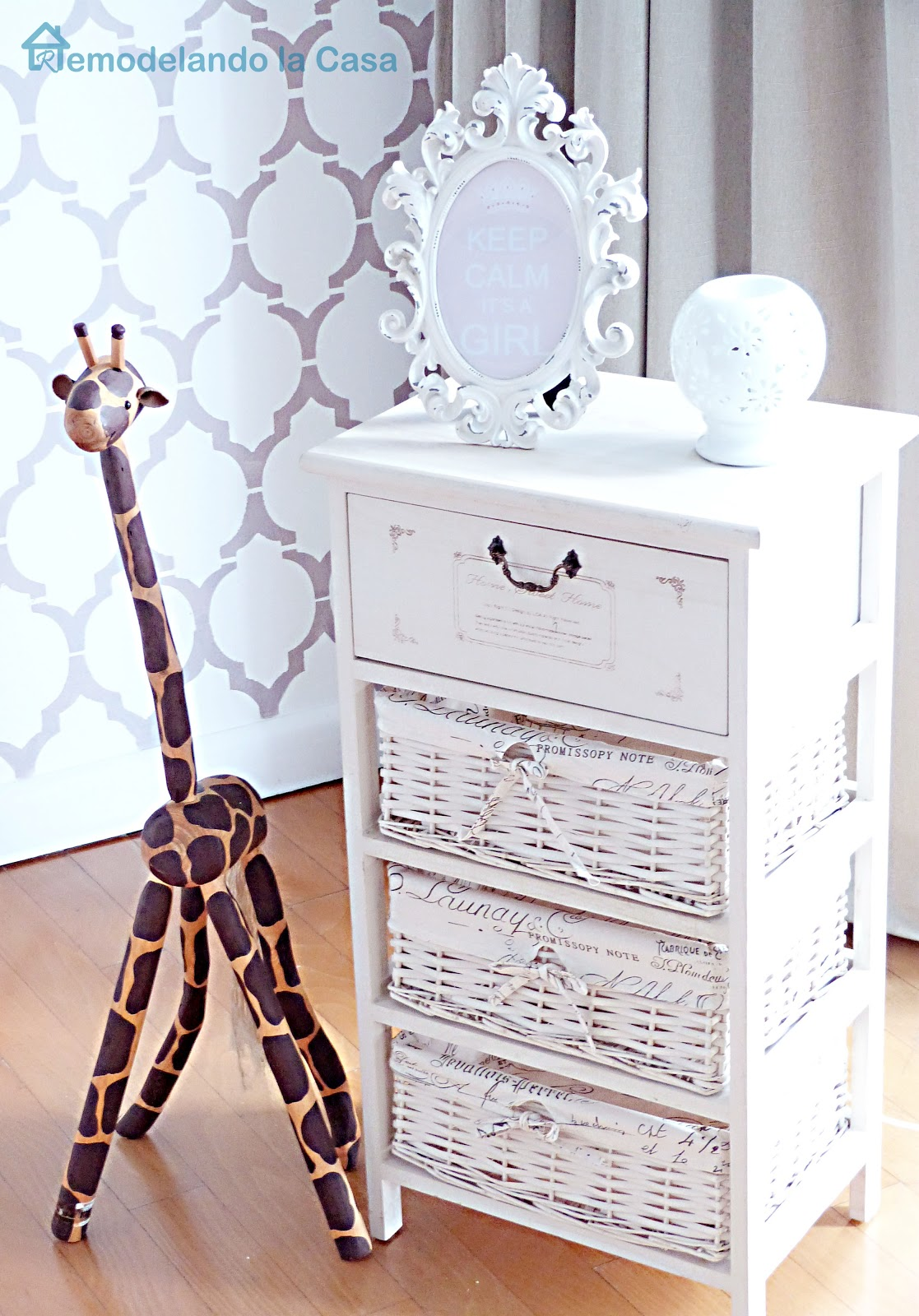 storage baskets and giraffe toy in baby girl nursery