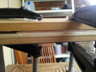 Serrage en cours de planches en bois collées entre-elles.
