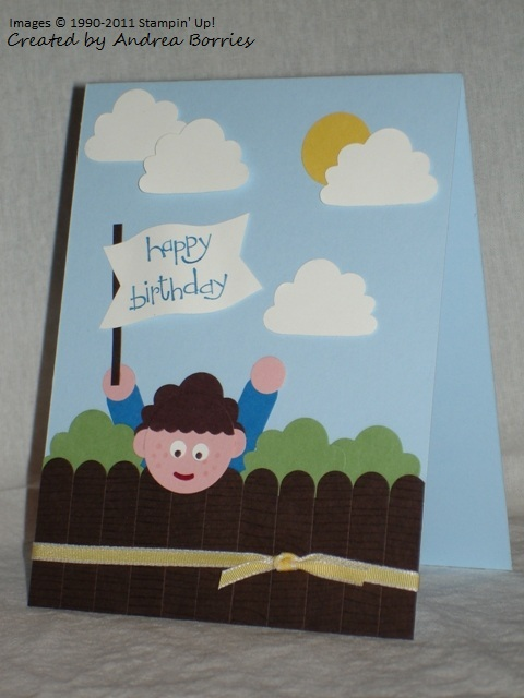 Punch art card with a fence, bushes, a boy waving a banner, sun and clouds made with punches.