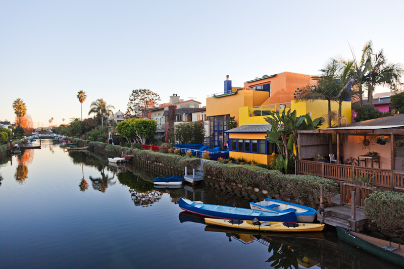 A reflection of boats and colorful houses along the Venice Canals in Venice, California
