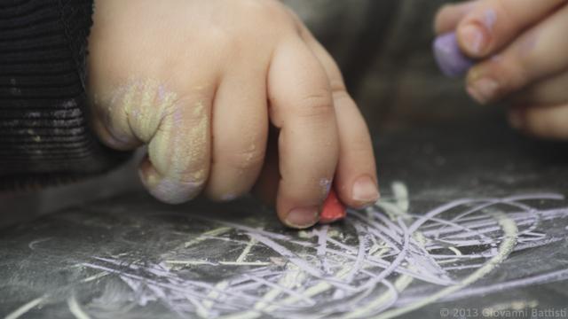 Mani di bimbo che disegna con i gessetti colorati