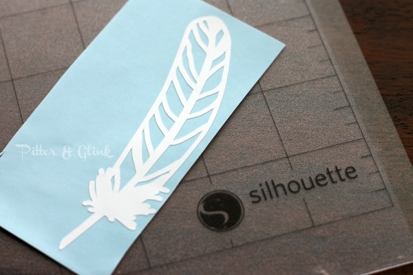 A feather cut from vinyl is used to create easy DIY art.  pitterandglink.com