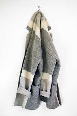 muted coloured single-breasted wool jacket hanging on an s-hook