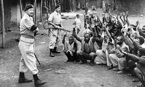 British soldiers with guns raised against black Africans