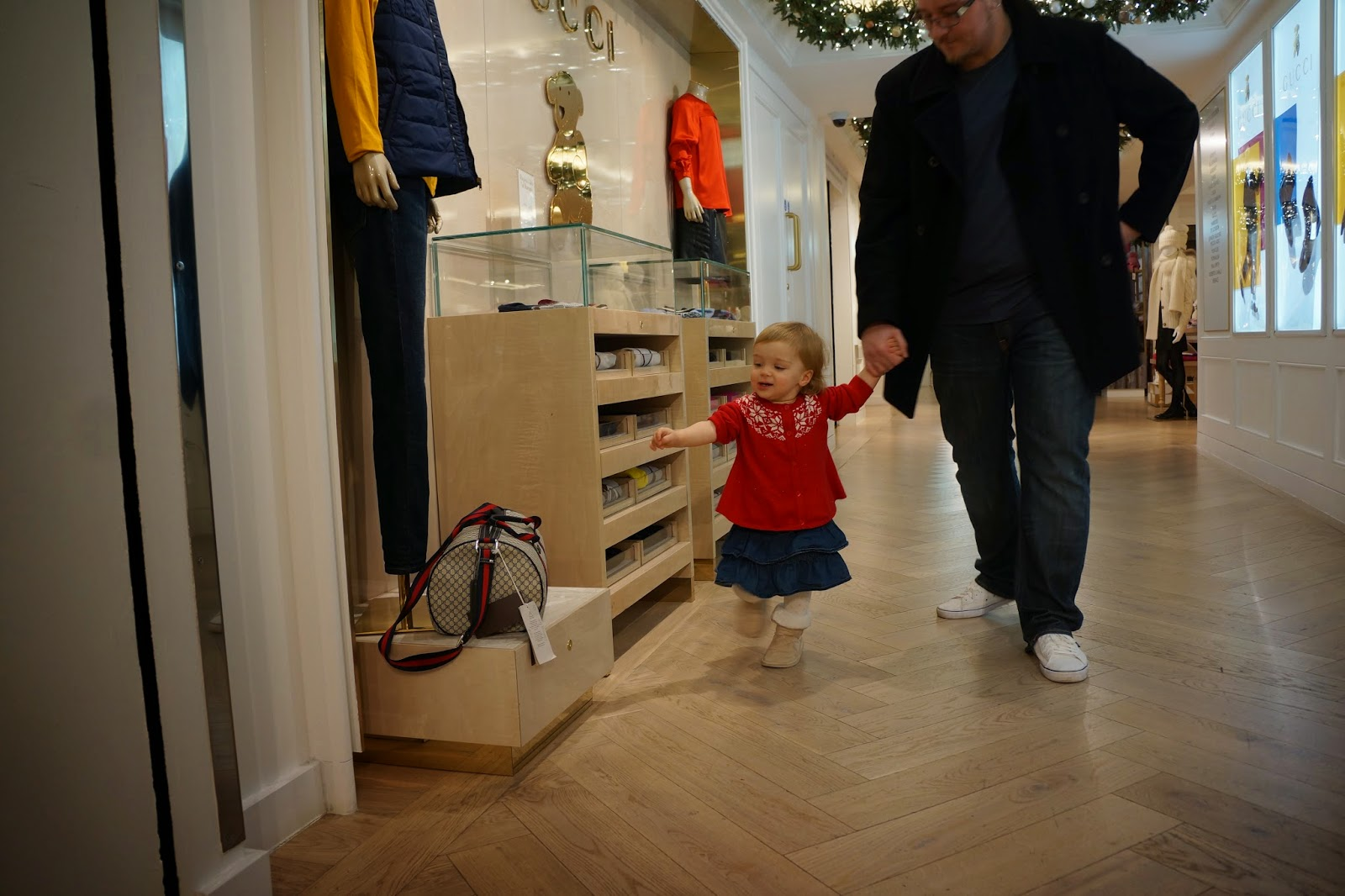 toddler reaching for gucci bag harrods