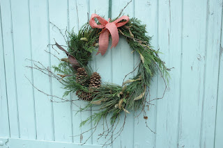 Freshly cut evergreen wreath with pine cones, magnolia and silver birch twigs.