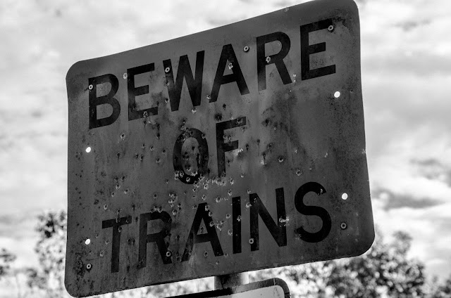 shotgun damaged beware of trains sign