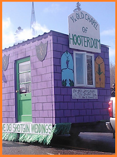 """Ye Old Chapel of Hooterdom"" float: purple building with a green door, plumes of smoke rising from it."