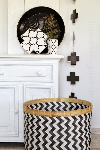 Eine schwarze Kreuzgirlande hängt von der Decke daneben eine weiße Kommode mit einem Holzkreuz mit grafischem Muster