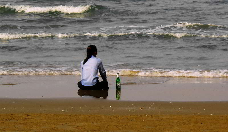 Sitting on the beach with a bottle of beer.