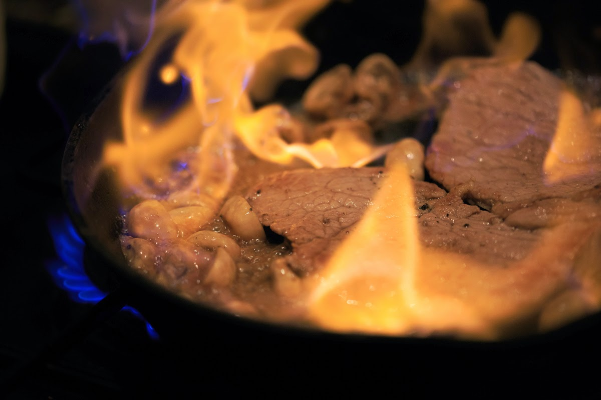 A frying pan of veal being flambeed with brandy