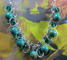 Necklace has emerald green czech beads and bigger turquoise beads encircled in silver rings