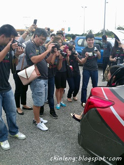Everyone taking picture of the pretty girl in the trunk