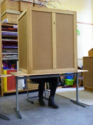Wahlkabine auf Schultisch, darunter blickdichte, schwarze Strümpfe und schwarze Stiefeletten.