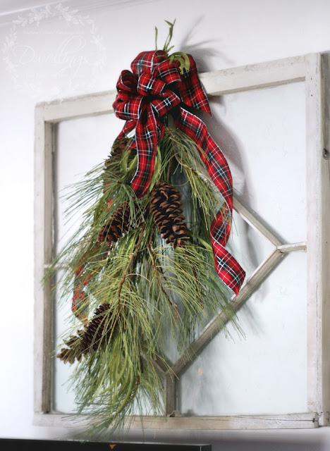 Antique window with plaid ribbon bow and pine cone garland.