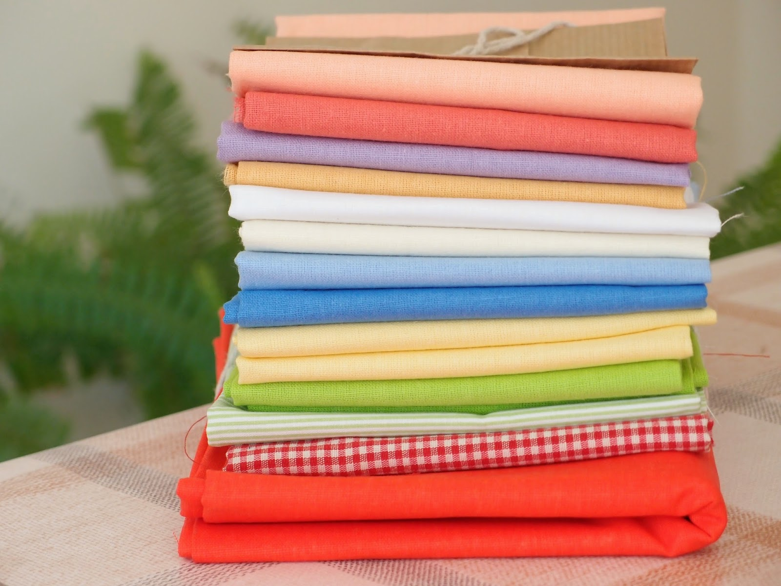 pile of fat quarters for an order - a building of fabric