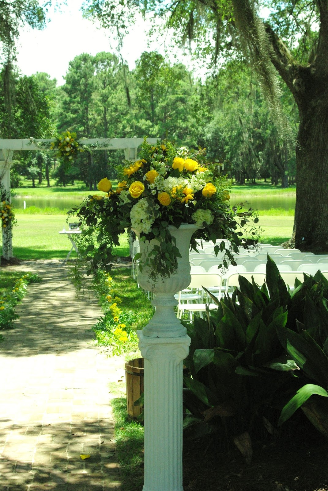 White Garden Urns Filled With Hydrangea Yellow Roses And Sun Flowers