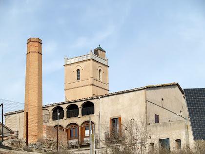 La façana de migdia de Can Oliveres, en la que destaca la gran balconada i la galeria porxada. També hi veiem la torre que corona l'edifici i la xemeneia de l'antiga alcoholera