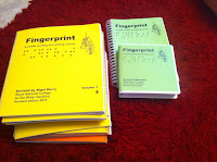 Fingertips braille course unpackaged, a pile of yellow braille books, a green box of CD's and a large print book