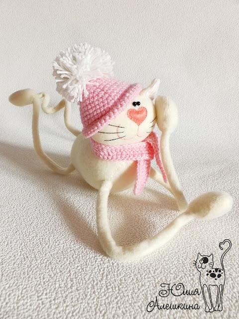 Кошка длинноножка бежевая в розовой шапочке. Мечтает