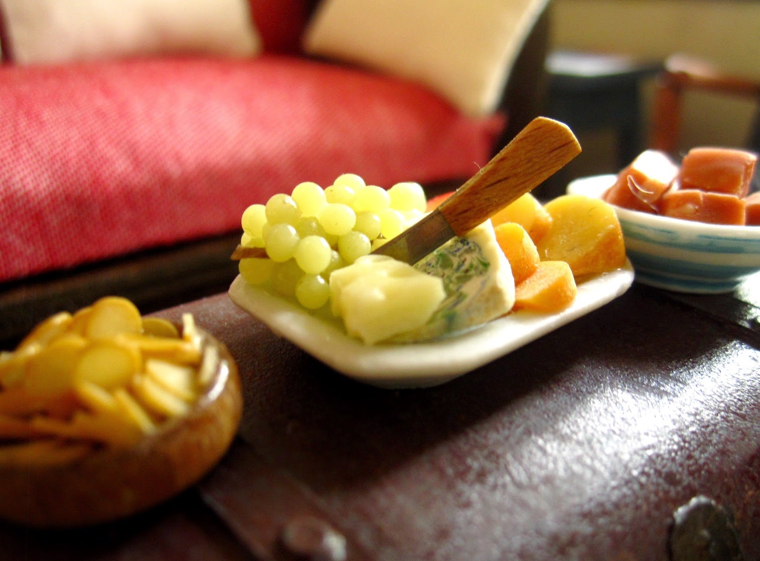 Miniature dolls' house finger food arranged on a coffee table, including a bowl of chips, a cheese and grape platter and a bowl of fudge,