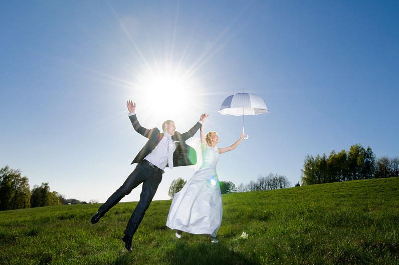 Linksma vestuvių fotosesija su baltu skėčiu