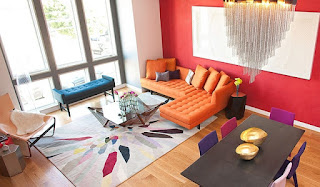 Colorful Sitting Space with Orange Modern Sofa Bed and Blue Bench near Glass Table on Colorful Carpet