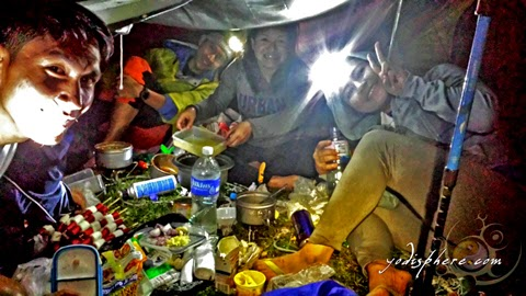 Mountaineers preparing dinner at the campsite of Mt. Ugo against a makeshift tent hover_share