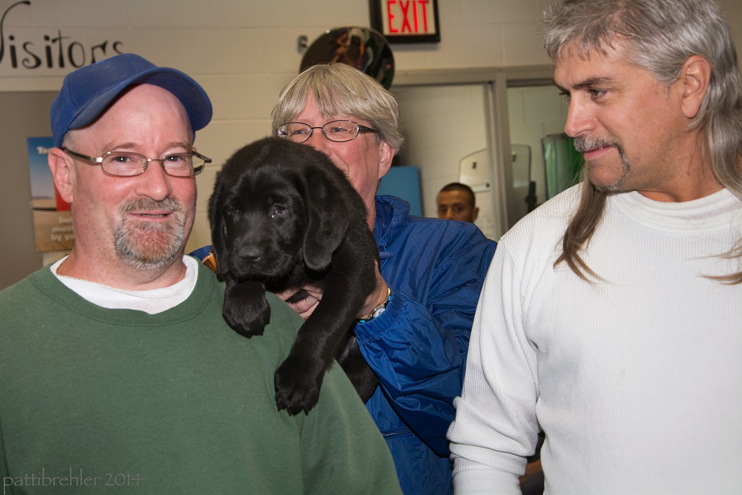 A man wearing a green sweatshirt and a blue ball cap and glasses is facing the camera on the left. On the right is a man wearing a white long sleeved tshrit. He is looking at the other man. Between them and behind them is a woman with short white hair and glasses, wearing a blue windbreaker. She is holding a small black lab puppy over the left shoulder of the man on the left. The puppy'es front paws are reaching over the man's shoulder.