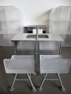 Modern dolls' house miniature white and grey kitchen set up, with concrete floor.