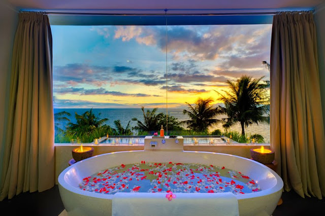 Picture of the bathtub by the window overlooking the sunset and the ocean