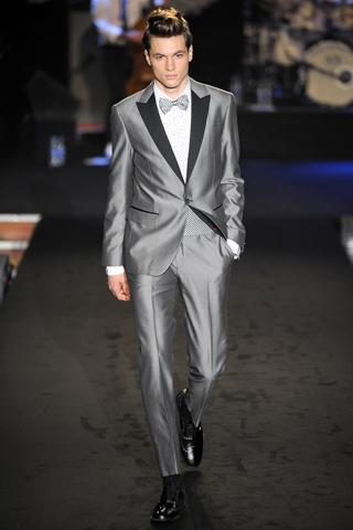 Traje esmoquin en color gris con mucho brillo. Solapa bi color negro y gris, en el bolsillo lleva un detalle de color negro y el moño es gris suave.