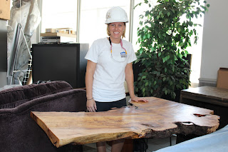 Stacy displays the wooden table she worked hard to complete!