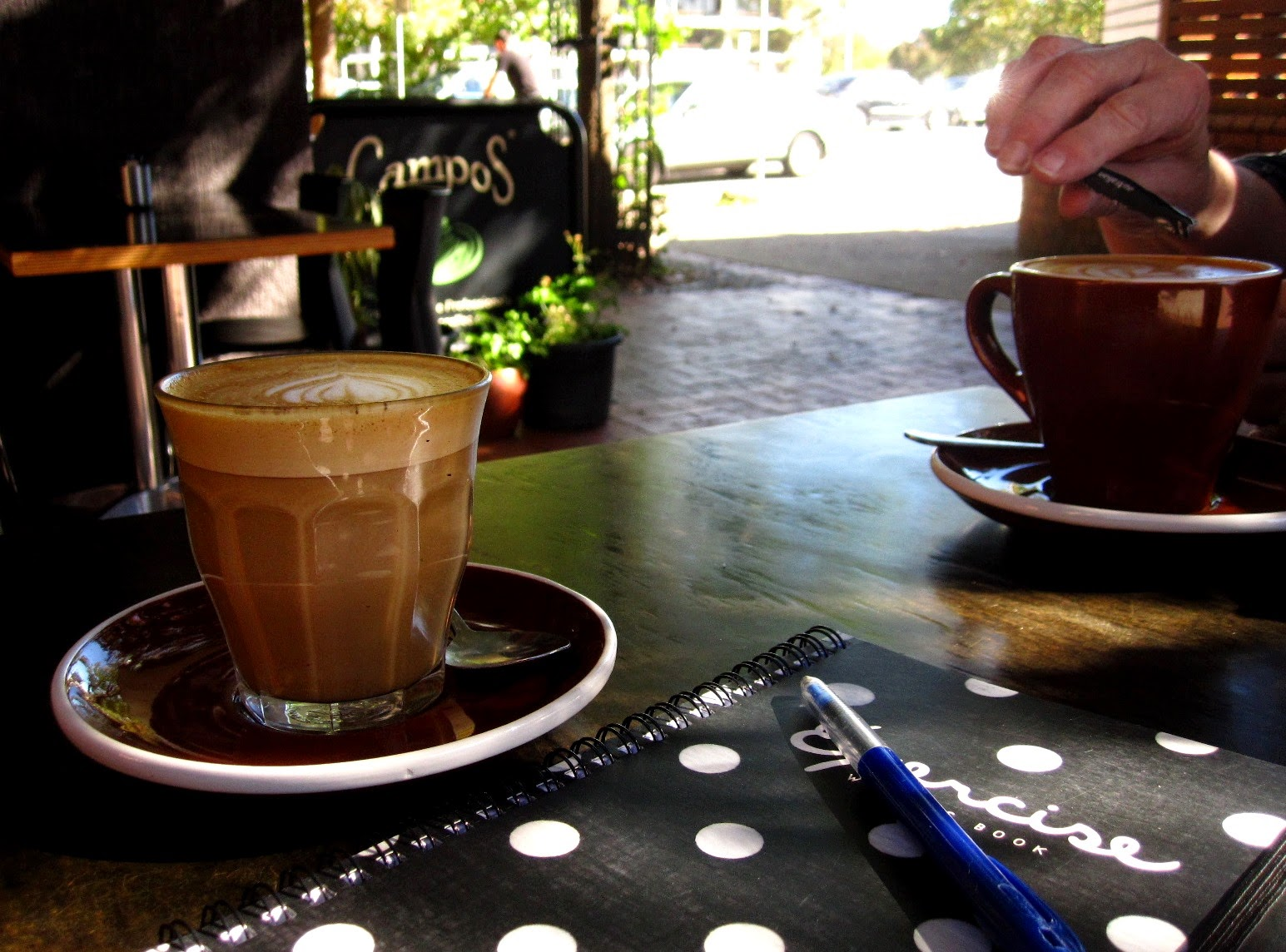 Two cups of coffee and a notebook on an outdoor cafe table.