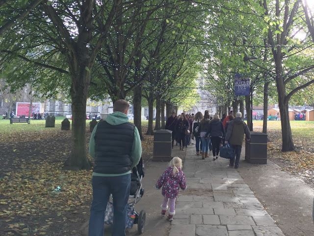 Mr Tin Box and Tin Box Tot walking through an avenue of decorated trees