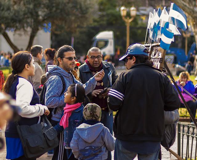 En plaza de Mayo un joven comprando una escarapela a un  vendedor callejero, rodeados de curiosos.