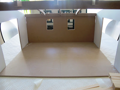 A half-built dolls' house shed from the front.