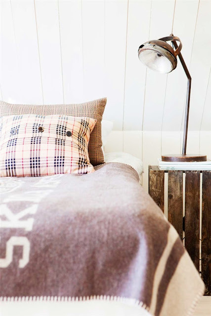 close up of plaid pillow case and wood panel container converted into a nightstand